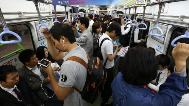 Commuters use smartphones in the subway