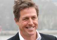 Hugh Grant smiles at a charity photo call in London